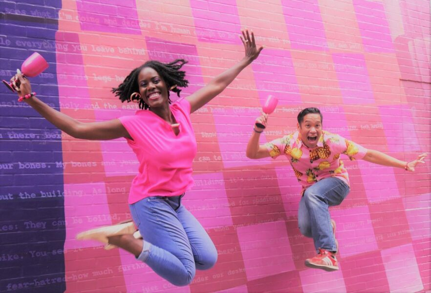 Jaylene Clark Owens and Justin Jain jump into the air in front of a pink mosaic mural